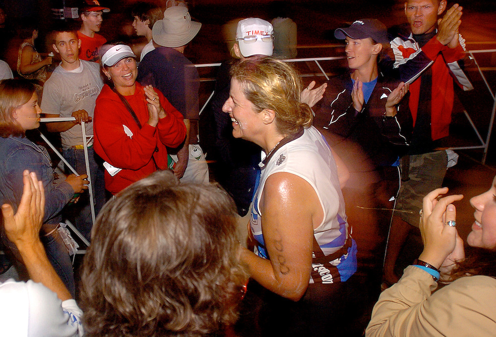 JEROME A. POLLOS/Press..Jo Walker, of Bellvue, Wash., makes her way to the finish line among cheering spectators two minutes after the midnight deadline for Ironman Coeur d'Alene.