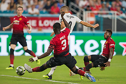 July 31, 2018 - Miami Gardens, FL, USA - Real Madrid forward Karim Benzema strikes on target as Manchester United captain Eric Bailly (3) slides to block the shot during the first half during International Champions Cup action at Hard Rock Stadium in Miami Gardens, Fla., on Tuesday, July 31, 2018. Manchester United won, 2-1. (Credit Image: © Sam Navarro/TNS via ZUMA Wire)
