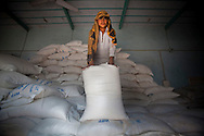 A workers stands on top of sacks of of food in the WFP warehouse to distribute to beneficiaries, on 21 February, 2011, in Umid Ali Junejo, Pakistan. (Photo by Warrick Page for CBC)