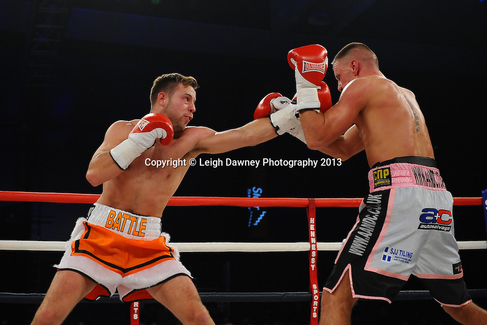 Adam Battle delivers a left on Chris Jenkinson during a Light Middleweight contest. Glow, Bluewater, Kent, UK. Hennessy Sports © Leigh Dawney Photography 2013.