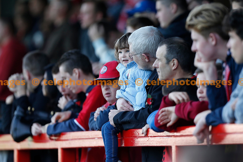 A young fan watches the Sky Bet League 2 match between Crawley Town and York City at the Checkatrade.com Stadium in Crawley. October 31, 2015.<br /> James Boardman / Telephoto Images<br /> +44 7967 642437