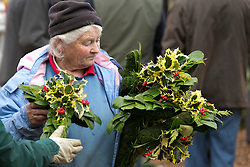 © Licensed to London News Pictures. 10/12/2013. Tenbury, Shropshire, UK. Pictured, buyers carry off their items. The last auction this year of Mistletoe and Holly took place in Tenbury today. The age long traddition of selling Mistletoe and Holly takes place every year in the town of Tenbury that sits on the Shrophire border. The sale which attracts farmers and wholesalers from around the area is organised by auctioneer Nick Champion who has presided over the sale for many years. Photo credit : Dave Warren/LNP