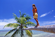 A girl stands on a coconuts tree in Marshall Islands / Majuro Atoll