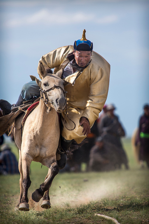 A Mongolian man wearing a traditional Mongolian deel; leans over his horse attempting to grab a wooden switch off of the ground while riding at a full gallop after the Naadam Festival at the Three Camel Lodge in the Gobi Desert of Mongolia on July 31, 2012. Horsemanship is very important to the Mongolian culture and this extra-festival sport has grown out of the fact that horse racing is considered one of the ?Three Manly Sports? practiced during the Naadam Festival. © 2012 Tom Turner Photography