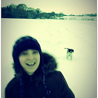 Female youth playing in the winter snow with a small dog following