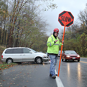 10/30/12 - Newark, DE - Hurricane Sandy - A flagger warns drivers to slow down while a white mini van sit damaged after hitting a tree head on Tuesday, Oct. 30, 2012, on Sunset Lake Rd in Newark DE...The driver was not injured.  ..SAQUAN STIMPSON/Special to The News Journal