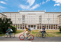 Cyclists ride  past historic socialist former East German apartment buildings on Karl Marx Allee in Berlin Germany