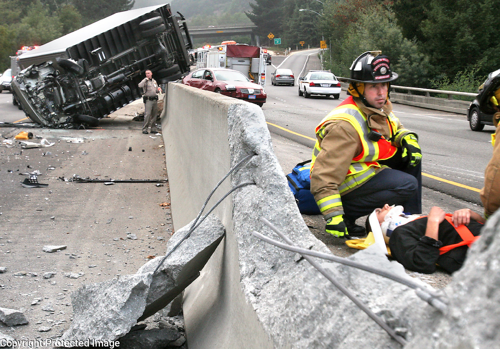 Scotts Valley firefighters wait for an ambulance to arrive as they stabilize the driver of a red Nissan Maxima who reportedly bumped the overturned delivery truck at top, sending oth cars careening out of control on Highway 17 in Scotts Valley, California on Monday November 5, 2007.