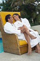 Couple in bathrobes relaxing in chair by pool