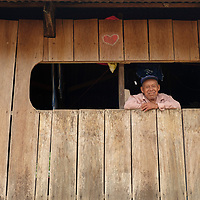 An older man smiles from the window of his home in the small community of San Francisco de Loreto on the Marañon River in the Peruvian Amazon.