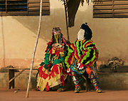 "EXCLUSIVE PICTURE FEATURE<br /> The Living Ghosts of Benin<br /> <br /> *Villagers believe if they are touched by an Egungun, they will die<br /> <br /> *Having any contact whatsoever with an Egungun can prove deadly for both the Egungun and the other person, so each Egungun is accompanied by a 'minder', also a member of the Egungun society, who carries a long and substantial stick to drive individuals away...<br /> <br /> <br /> <br /> BENIN is a small country sandwiched between Nigeria to the East and Ghana and Togo to the West. Formerly a French colony known as Dahomey, little is known about the country prior to around the 15th century when it was occupied first by the Portuguese, then the British, Dutch and lastly French who ousted King Behanzin and took control in 1894. <br /> <br /> The Egungun are one of Benin's Secret Societies who appear as masked men representing the spirits of the Living Dead. They are Living Ghosts, a conduit to the ancestors. Their role in village society is to settle local disputes, and their knowledge is often consulted in times of trouble within their village. The Egungun speak in a high-pitched and altogether un-human and unsettling falsetto tone, similar to the voices used in a Punch-and-Judy show, and in a language that is not understood by other villagers; they are always accompanied by drummers. Some say they derive their name from the Yoruba (Northern Nigerian) word for ""bones"" or ""skeleton,"" but in Yoruba, Egungun also means ""masquerade.""  Egungun arrive in villages, pass judgements and give advice. Their word is final as their advice is a direct word of the Gods.<br /> <br /> Each Egungun appears as a robed figure - giving the impression that the deceased is making a temporary reappearance on Earth. This impression is enhanced by the voluminous costumes of the Egungun; the cloth and design they use expresses the power of the ancestor. In one village I came across an Egungun with the stature and form of a child. I enquired as to his age (all Egungun are male). As soon as I'd asked I realised that"
