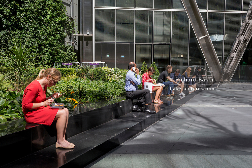 City workers enjoy their lunches in summer sunshine on Primrose Street in the City of London, the capital's financial district - aka the Square Mile, on 8th August, in London, England.