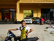 """13 FEBRUARY 2019 - SIHANOUKVILLE, CAMBODIA: A worker at the BWin Casino, a newly opened casino in downtown Sihanoukville, waits to take a co-worker home after their overnight shift in the casino. There are about 80 Chinese casinos and resort hotels open in Sihanoukville and dozens more under construction. The casinos are changing the city, once a sleepy port on Southeast Asia's """"backpacker trail"""" into a booming city. The change is coming with a cost though. Many Cambodian residents of Sihanoukville  have lost their homes to make way for the casinos and the jobs are going to Chinese workers, brought in to build casinos and work in the casinos.      PHOTO BY JACK KURTZ"""