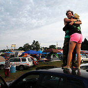 Laurel Stinson, 25, of Long Island, right, embraces with friend Travis Calkins, 22, of Colorado, left, early morning at the 2013 Electric Forest Festival at The Double JJ Ranch in Rothbury Mich., on June 28, 2013.