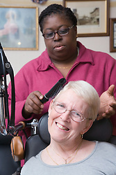 Carer helping woman with cerebral palsy with personal care,