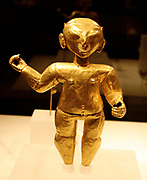 Standing figure.  Ecuador or Colombia, Tolita-Tumaco. 1st-4th century, hammered gold.  Three dimensional figures in the Tolita-Tumaco style are among the most unusual Precolumbian gold objects.  The figure displayed here is distinguished by its decorated nose ornament.  the Tolita-Tumaco style area style area is located on the Ecuador-Colombian border along the Pacific coast.