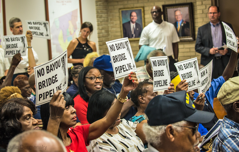 Residents of St. James Parish at a St. James Parish Council meeting on August 23, 2017, in Vacherie, Louisiana holding up signs in opposition of  the Bayou Bridge pipeline.