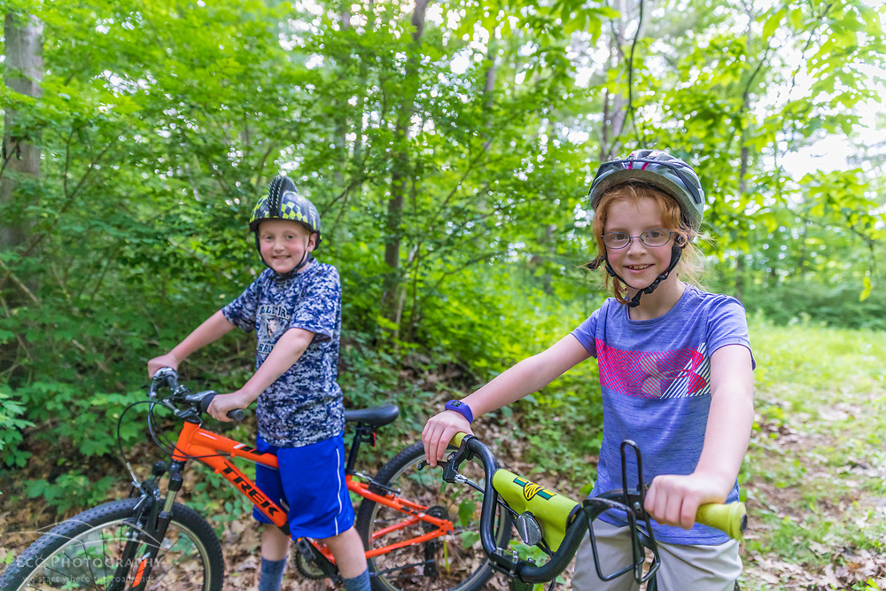 A boy and girl ride their mountain bikes in a forest at the Donibristle Reservation in Topsfield, Massachusetts.