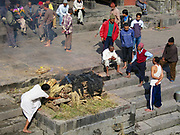 Kathmandu, Nepal - November 27, 2005: Unidentified people take part in traditional cremation ceremony at the Pashupatinath temple on the Bagmati River bank in Kathmandu, Nepal.