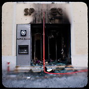 The burned out remains of 'Sprider', a shop on Ermou Street.<br /> <br /> Following the murder of a 15 year old boy, Alexandros Grigoropoulos, by a policeman on 6 December 2008 widespread riots, protests and unrest followed lasting for several weeks and spreading beyond the capital and even overseas<br /> <br /> When I walked in the streets of my town the day after the riots I instantly forgot the image I had about Athens, that of a bustling, peaceful, energetic metropolis and in my mind came the old photographs from WWII, the civil war and the students uprising against the dictatorship. <br /> <br /> Thus I decided not to turn my digital camera straight to the destroyed buildings but to photograph through an old camera that worked as a filter, a barrier between me and the city.