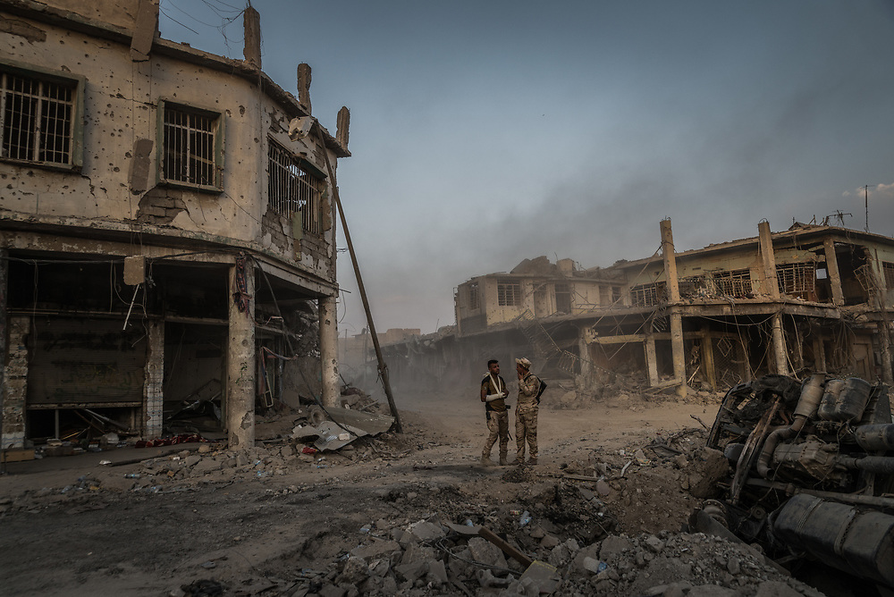 Iraqi soldiers stand surrounded by the ruins of the Old City of Mosul as the battle to liberate the remaining pocket of ISIS-held territory continues.