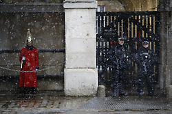 © Licensed to London News Pictures. 10/12/2017. London, UK. A soldier and armed police officers are on patrol at Horse Guards Parade London during a heavy snowfall on Sunday, 10 December 2017. Photo credit: Tolga Akmen/LNP