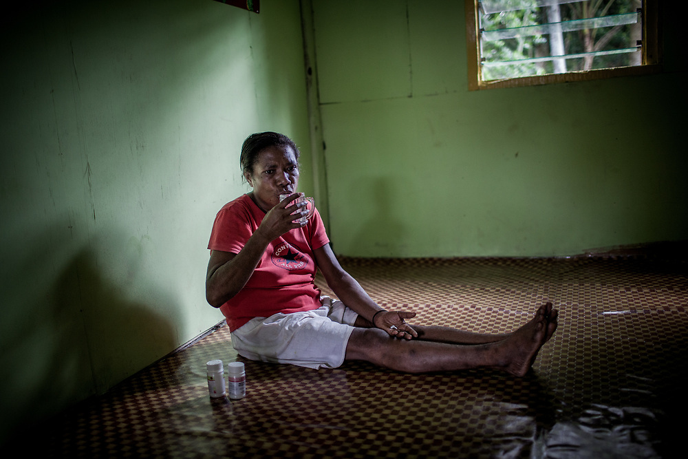 Mama Yuli takes her ARV pills at eight o&rsquo;clock every morning for the last eight years.<br /> <br /> In 2004 Mama Yuli contracted the HIV virus from her husband who later died from AIDS. At her worst point, Mama Yuli was just skin and bones weighing only 22 kilograms (48 pounds). With ARV she is now healthy to work and support her family.<br /> <br /> If taken properly and regularly, ARV has been proven to prolong the survival rate of people living with HIV/AIDS and enables them to live a productive life. The Indonesian government started providing ARV therapies in 2003. In that year only 7 packages of ARV were purchased for all of Papua. Each package cost approximately $5000. Today in Indonesia this vital medication can be obtained at no cost only in Papua but only 12% of those with HIV/AIDS are undergoing ARV therapy.<br /> <br /> Despite these advances, ARV is mostly available only in cities. Collaboration between health facilities in urban centers and staffs in rural areas to make ARV more accessible for patients living in the countryside is still lacking as well as the endorsement of ARV as a legitimate medicine for HIV/AIDS. Sometimes health staff and even educational materials still provide misleading information and perception such as &quot;there is no medicine for HIV/AIDS.&quot;<br /> <br /> As a general practice health personnel often evaluate patients for their adherence in taking their medication and keeping up with appointments before allowing them to undergo ARV therapy. Indigenous Papuans tend to fall short of this assessment and fail to return for their check-up because many of them live too far from the health centers.  At times, they do not fully understand the benefits of ARV medication and the importance of taking them properly due to poor counseling from the health staff.  Also, many of them are unable to keep their appointments or take medication regularly because they still keep their status a secret from their immediate family members o