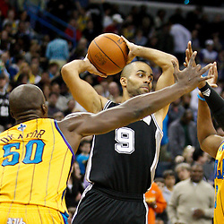 January 22, 2011; New Orleans, LA, USA; San Antonio Spurs point guard Tony Parker (9) is defended by New Orleans Hornets center Emeka Okafor (50) and point guard Chris Paul (3) during the third quarter at the New Orleans Arena. The Hornets defeated the Spurs 96-72.  Mandatory Credit: Derick E. Hingle