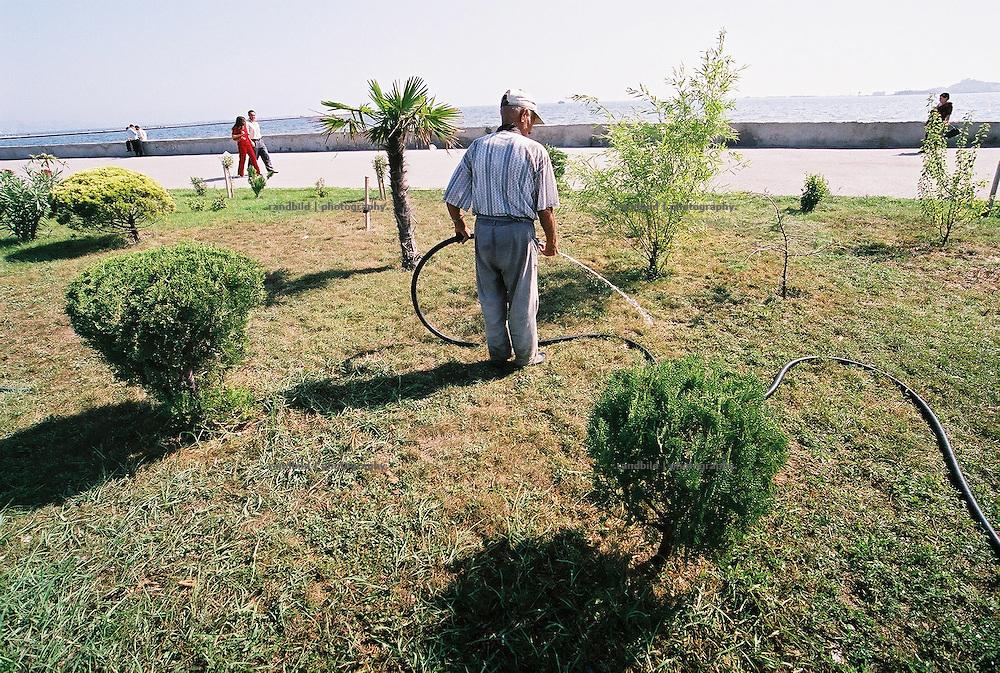 In der aserbaidschanischen Hauptstadt Baku bewässert ein Mann den Grünstreifen der Promenade am Kaspischen Meer. A man waters plants at a promenade in Baku