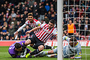 Neal Maupay (Brentford) moves forward to get the ball released by Kelle Roos (GK)(Derby County) who then regains hold of the ball assisted by Richard Keogh (Capt)(Derby County) watched by Oliver Watkins (Brentford) during the EFL Sky Bet Championship match between Brentford and Derby County at Griffin Park, London, England on 6 April 2019.