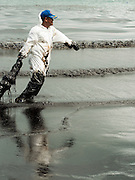 30 JULY 2013 - KOH SAMET, RAYONG, THAILAND:  A worker pulls an oil soaked boom through oily surf on Ao Prao beach on Koh Samet island. About 50,000 liters of crude oil poured out of a pipeline in the Gulf of Thailand over the weekend authorities said. The oil made landfall on the white sand beaches of Ao Prao, on Koh Samet, a popular tourists destination in Rayong province about 2.5 hours southeast of Bangkok. Workers from PTT Global, owner of the pipeline, and up to 500 Thai military personnel are cleaning up the beaches. Tourists staying near the spill, which fouled Ao Prao beach, were evacuated to hotels on the east side of the island, which was not impacted by the spill. PTT Global Chemical Pcl is part of state-controlled PTT Pcl, Thailand's biggest energy firm.     PHOTO BY JACK KURTZ