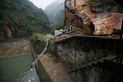 A view of a road that was damaged by fallen rocks as Chinese rescue workers try to remove a boulder blocking a road to Taiping town of Lushan County, Sichuan Province, China, 23 April 2013. Landslides and fallen rocks block vital roads carrying supplies to remote towns and villages affected by the earthquake. The Lushan Earthquake in Sichuan Province on 20 April 2013 resulted in 186 people dead, 21 missing, 11248 injured. About 1.72 million people were affected by the quake, while an initial estimate by the International Red Cross on Saturday put the number needing emergency shelter, water and food at 120,000. The China Earthquake Administration (CEA) recorded a magnitude 7.0 earthquake, while the US Geological Survey said it had measured 6.9.
