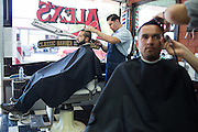 Owner Alex Franco trims Fremont resident Hector Pineda's hair at Alex's Classic Barber Shop & Shaves in Fremont, California, on April 9, 2014. (Stan Olszewski/SOSKIphoto)