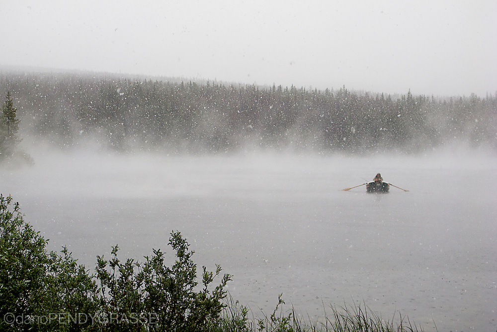 A fisherman in his pram braves a freak summer snowstorm on a lake in British Columbia's high country.