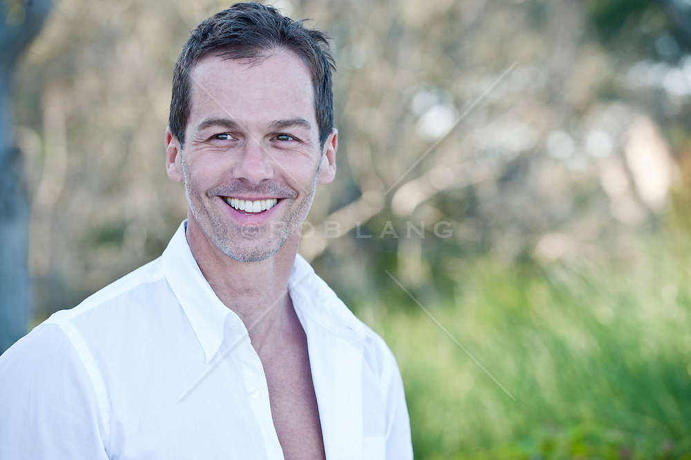 handsome middle aged man outdoors near trees and grassy area on a beach in South Carolina