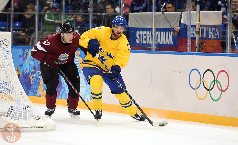 Feb 15, 2014; Sochi, RUSSIA; Sweden forward Daniel Sedin (22) carries the puck against Latvia forward Martins Vipulis (47) in a men's preliminary round ice hockey game during the Sochi 2014 Olympic Winter Games at Shayba Arena.