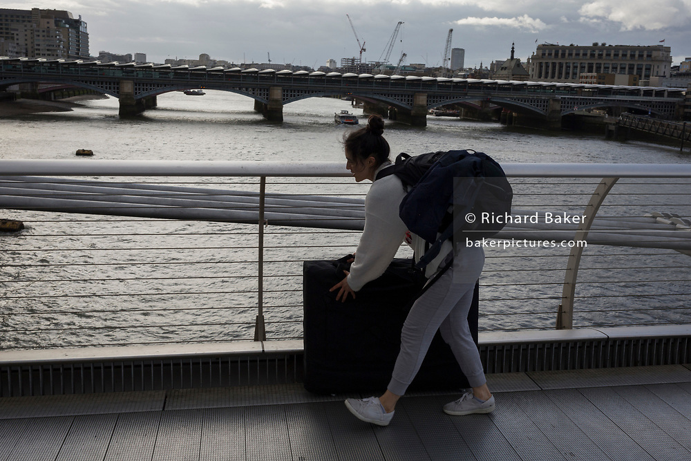 As the UK government announces further Coronavirus-related restrictions to its citizens, with the immediate closure of pubs, cafes, gyms and cinemas, and the worldwide number of deaths reaching 10,000 with 240,000 cases, 953 of those in London alone, a young woman pushes a heavy object across the Millennium Bridge, on 20th March 2020, in London, England.