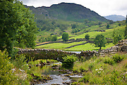 Packhorse Bridge across mountain stream at Watendlath in the Lake District National Park, Cumbria, UK