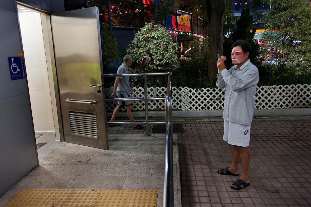 An actor from a small opera company from Chaozhou, China is using the light of public toilets to make up. <br />