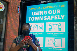© Licensed to London News Pictures. 13/06/2020. WATFORD, UK. A woman wearing a mask in front of a social distancing instructional screen in Watford High Street.  To try to stimulate the economy, the UK Government is easing coronavirus pandemic lockdown restrictions to permit non-essential shops to re-open on 15 June, but only if they are Covid19 compliant.  Shoppers will also need to practice social distancing.  After a record 20.4% reduction in gross domestic product (GDP) in April, the country is on course for the worst recession in more than three centuries.  Photo credit: Stephen Chung/LNP