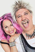 Portrait of senior punk couple with man sticking out tongue over gray background