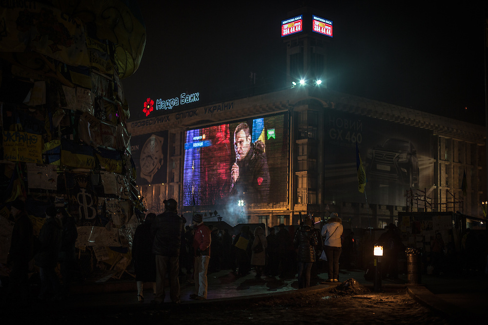 Protesters watch Vitali Klitschko's speech, on the giant screen of the Independance Square.