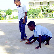 Local Anguillan boys play marbles after school..British West Indies