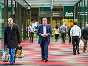 03 MAY 2017 - MINNEAPOLIS, MN: People leaving the IDS Center, the hub of the Minneapolis skyway system. The skyways are enclosed pedestrian overpasses that connect downtown buildings. The Minneapolis Skyway was started in the early 1960s as a response to covered shopping malls in the suburbs that were drawing shoppers out of the downtown area. The system grew sporadically until 1974, when the construction of the IDS Center and its center atrium, called the Crystal Court, served as a hub for the downtown skyway system. There are 8 miles of skyways, connecting most of the downtown buildings from Target Field (home of the Minnesota Twins) to US Bank Stadium (home of the Minnesota Vikings). In the last five years many upscale downtown apartment buildings and condominium developments have been added to the system, allowing downtown residents to live and work downtown without going outside.     PHOTO BY JACK KURTZ