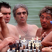 A group of men gather around a chess game being played on a cork board at the Szechenyi public mineral baths in Budapest, Hungary.  @1993