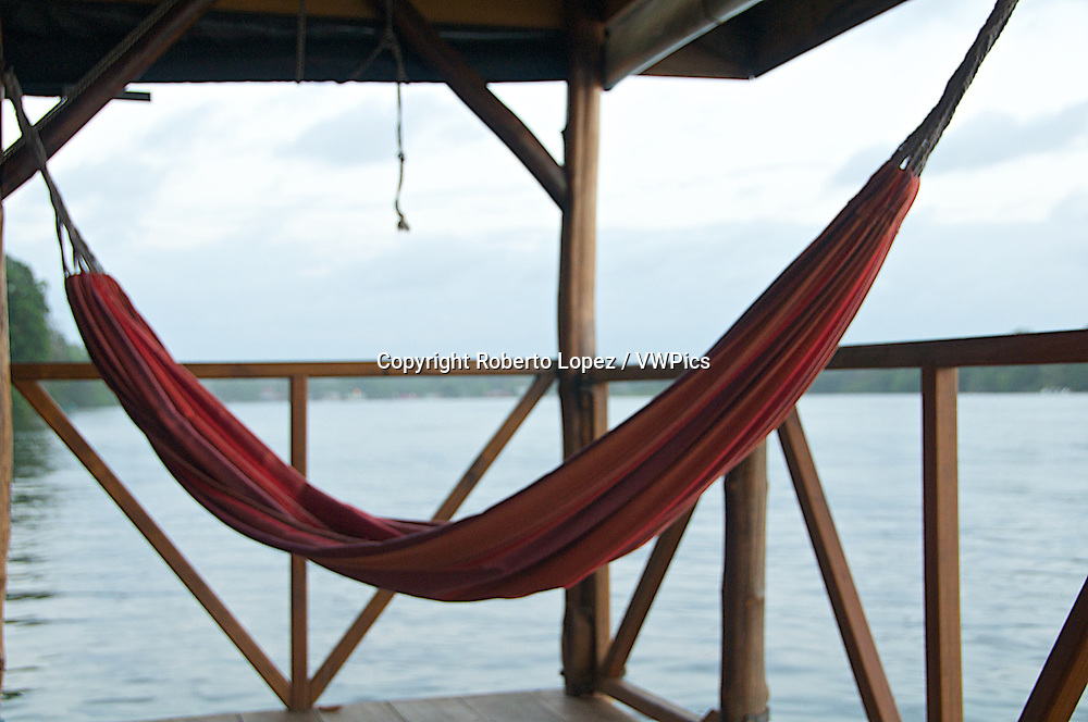 Red hammock with a peaceful view of the Tortuguero River, at the Mawamba Lodge, Costa Rica.