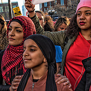 Yemen Muslim mother and daughter in crowd listening to speaker on stage during rally.<br /> <br /> Women took to the streets of Manhattan Wednesday, March 8, 2017, in a show of solidarity with International Women's Day and the A Day Without a Woman strike and to voice their anger again at President Trump.<br /> <br /> New Yorkers both men and women attended rally at Washington Square Park holding signs in protest against President Trump.