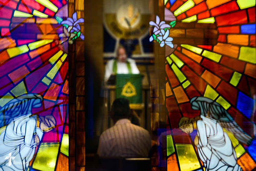 The Rev. Bill Qualman, pastor at Mt. Calvary Lutheran Church, La Grange, Texas, preaches during Divine Service at the church on Sunday, Sept. 3, 2017. Qualman is seen through a window reflecting stained glass on the church doors. Last week, only a handful of church members who weren't trapped by the floodwaters made it to worship. A week after Hurricane Harvey the pews filled up again after the waters receded. LCMS Communications/Erik M. Lunsford