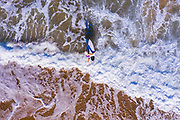 Aerial photo of a woman with a surfboard and a long late afternoon shadow running into the surf at Shelly Beach, Sunshine Coast, Queensland, Australia