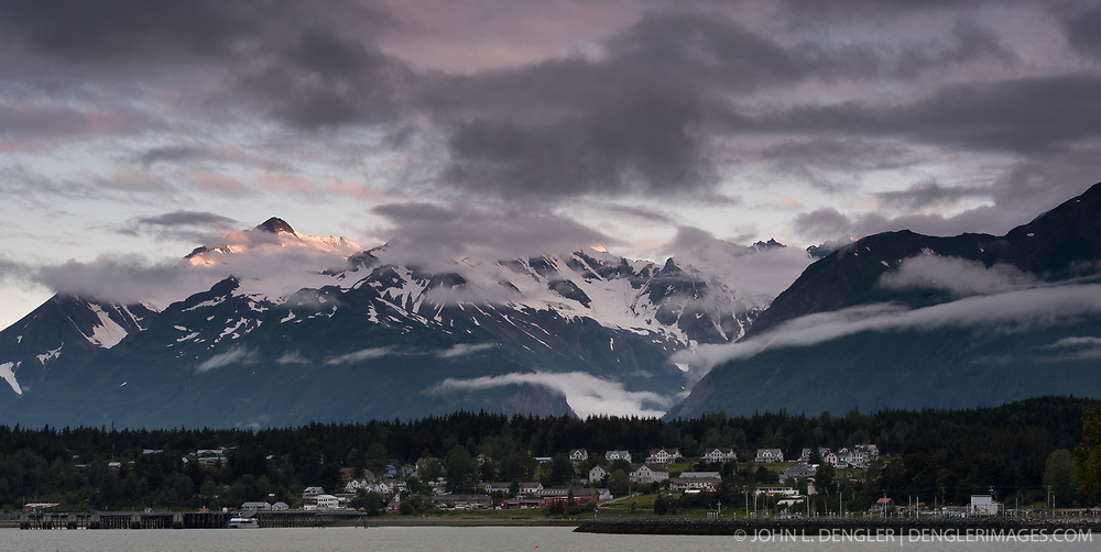 """The sun sets on the mountains of the Chilkat Range as seen from """"Picture Point."""" In the foreground are the buildings of the former U.S. Army fort, Ft. William H. Seward in Haines, Alaska."""